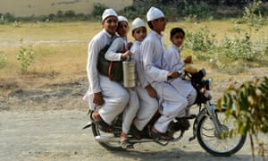 Q: How many brothers can you fit on a motorbike? A: Four - with room for a very small friend in this case. These boys are making their way home from school at a madrasa in Lahore in Pakistan.