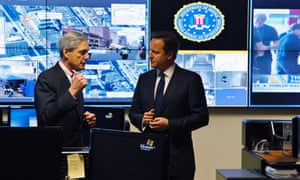FBI Director Robert Mueller (L) talks with Britain's Prime Minister David Cameron (R), as images from the bombings at the Boston Marathon are projected behind them, during a tour of the Strategic Information Operations Center (SOIC) at the headquarters of the Federal Bureau of Investigation in Washington.