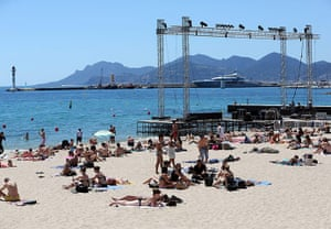 Cannes preparation : Sunbathers on the beach next to the giant Cinema de la Plage screen