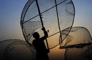 A Bahraini fisherman loads fish traps on his boat near the Persian Gulf seashore in the western fishing village of Malkiya, Bahrain.