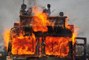 A fiery perspective: Indian labourers stand on top of a grain transport truck that caught fire after an oil leak leakage in Allahabad. Bad roads, speeding vehicles and poor driving are among the contributing factors to road accidents. Photograph: Sanjay Kanojia/AFP/Getty Images