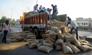 And slightly less dramatic angle as Indian labourers unload grain. Photograph: Sanjay Kanojia/AFP/Getty Images