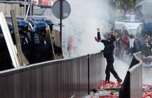 A PSG supporter throws a projectile at riot police as clashes brake out during the championship celebrations. Photograph: Franck Fife/AFP/Getty Images