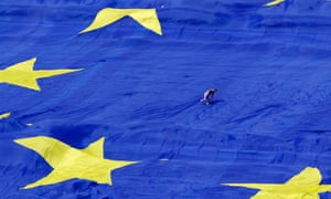 An organiser walks on a large European Union flag is displayed front of Romania's parliament. Today the Conservatives are publishing a draft EU referendum bill.