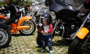 Petrol-head mini: wearing a helmet a young boy poses next to a Harley Davidson motorcycle during the annual Harley Davidson National Rally in Qian Dao Lake, in Zhejiang, China.