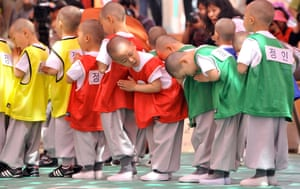 Young South Korean novice monks pray before playing a football match during a course called Children becoming Buddhist monks at the Jogye Temple in Seoul. The children are staying at the temple to learn about Buddhism.