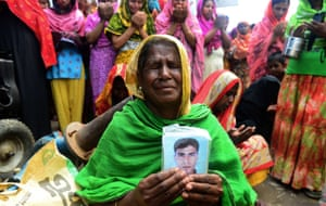 A Bangladeshi woman holds up the portrait of a missing relative as she offers prayers in front of the rubble of the collapsed factory in Savar, on the outskirts of Dhaka, Bangladesh. The army stopped its search for bodies in the building today.
