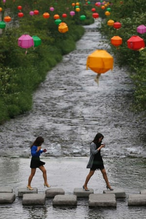 Women cross stepping-stones underneath lotus lanterns, which were hung-up in preparation for the up-coming of birthday of Buddha, along the Cheonggye stream in central Seoul, South Korea.