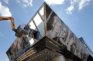Cannes preperations: Workers install giant posters on the facade of the Casino