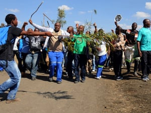 Striking Lonmin mine workers dance and sing as they gather next to a hill called Wonderkop this morning in Marikana, where 34 people were shot and killed by South African police during protest action for better wages in August last year. Thousands of mine workers downed tools today at the Lonmin mine after a union leader was shot dead at the weekend.