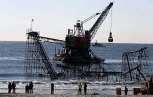 A barge moves into position as workers prepare to remove the Star Jet rollercoaster that has been in the ocean for six months after the Casino Pier it was built on collapsed when superstorm Sandy hit Seaside Heights, New Jersey.
