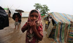 A girl from Thandawli village stands in the rain in front of a Rohingya internally displaced persons camp outside Sittwe, Burma. More than 100,000 displaced people could be relocated to avoid the approaching cyclone Mahasen, according to the United Nations.