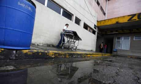 A body is taken to the morgue of a hospital in San Pedro Sula