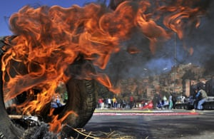 Burning issues: Workers block streets and highways as they march from El Alto to La Paz on the ninth day of an indefinite strike called by the Bolivian Workers' Centre (COB) to demand the government for a pension equivalent to 100% of their salaries. Photograph: Aizar Raldes/AFP/Getty Images