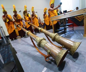 Tibetan monks blow on two dunchen as they perform a ground ceremony prior to starting the creation of a mandala (sand sculpture), as part of city-wide events for the visit of the Dalai Lama, who will be arriving in New Orleans.