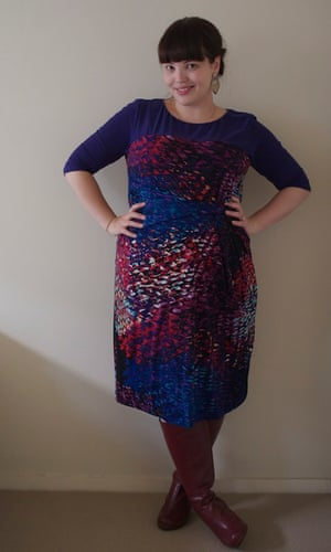 Woman with both hands on hips wearing a multicoloured dress with boots