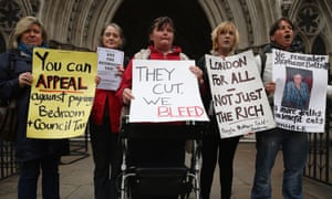 Demonstrators hold placards protesting against government changes to the welfare system and the proposed 'bedroom tax' outside the High Court in London, England. The tax is being challenged at the High Court by a group of families who care for disabled people, claiming discrimination as spare rooms used in coping with disability have resulted in welfare benefit cuts.