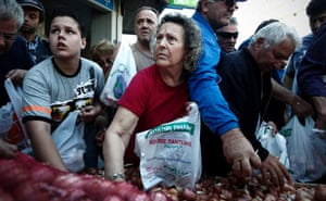 People take fruit and vegetables from a stall during a free produce distribution organized by farming producers and open market stall owners in Athens, Greece.