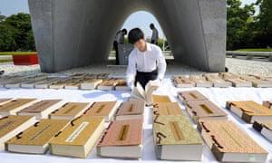 A Hiroshima City officer airs the name books of atomic bombs victims of Hiroshima and Nagasaki