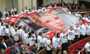 Ukrainian opposition deputies hold a large flag with the portrait of jailed former Prime Minister and the opposition leader Yulia Tymoshenko as they shout the slogan 'Freedom for Yulia!' during a speech by the Ukrainian President in the parliament in Kiev.