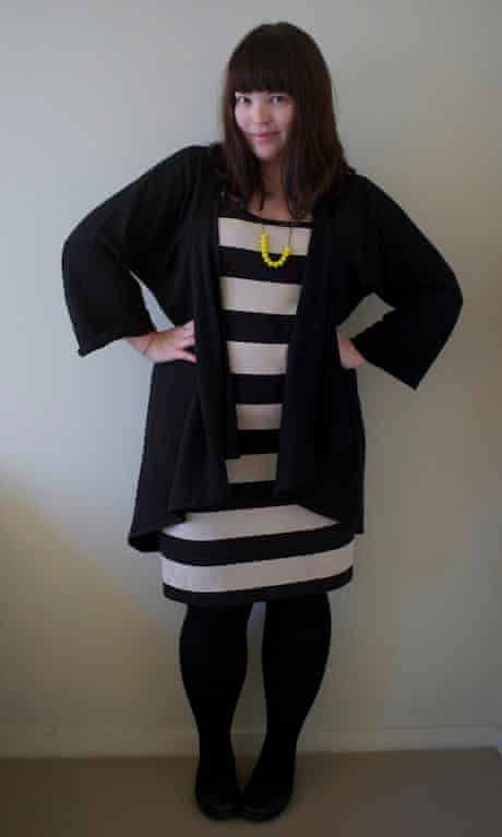 Woman wearing a black and white striped dress with long black cardigan open over the top