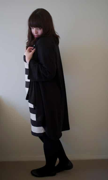 Woman wearing black and white striped dress with long cardigan standing sideways