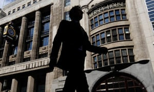 A pedestrian passes offices of Goldman Sachs in London