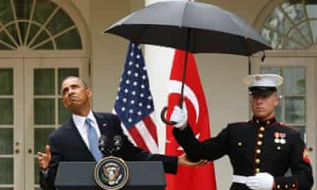Barack Obama checks to see if he still needs the umbrella held by a US marine.