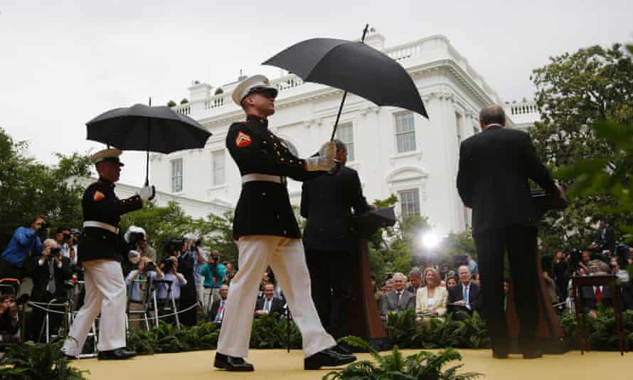US marines in dress uniform step onto the stage to shield Barack Obama and Turkey's Prime Minister Recep Tayyip Erdogan from a sudden dounpour