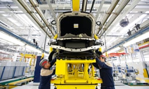 Employees work under the wheel arches of a Maserati Quattroporte luxury automobile as it travels along the production line at Fiat SpA's Grugliasco factory in Turin, Italy, on Wednesday, Jan. 30, 2013.
