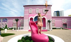 A FEMEN protester with an inscription on her body that reads: 'Life in plastic is not fantastic' holds up a burning cross with a Barbie doll attached to it while standing on a water fountain the shape of a giant pink shoe outside the Barbie Dreamhouse Experience in Berlin, Germany.