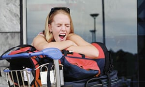 Jet lag. Young woman leaning on luggage on trolley, yawning