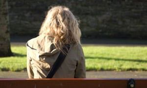 rear view young blonde woman sitting on park bench alone worried depressed