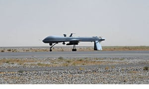 A US Predator drone armed with a missile stands on the tarmac of Kandahar military airport.