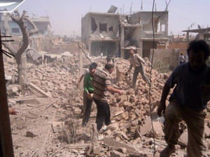 Syrians inspecting the rubble of damaged buildings after government air strikes against the western town of Qusair, in Homs province, Syria. The town  has been besieged for weeks by regime troops and pro-government gunmen backed by the Lebanese militant Hezbollah group.