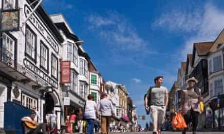 Shoppers in Guildford historic cobbled High Street enjoying the sunshine Guildford Surrey UK