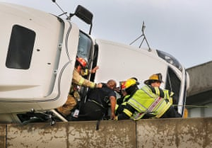 Tornado in USA: Firefighters assist a lorry driver as he is taken from his overturned truck