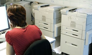 A woman working in an office near printers