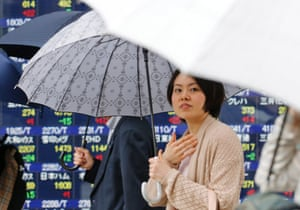 People under umbrellas walk by an electronic stock board of a securities firm in Tokyo, Monday, May 20, 2013. Japan's Nikkei 225 index jumped 1.4 percent to 15,352.84 as evidence of a steady economic recovery in the U.S. helped push Asian stock markets higher Monday.
