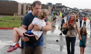 Teachers carry children away from Briarwood Elementary school in Oklahoma City after a tornado destroyed it on May 20.