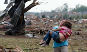 A woman carries a child through a field near the collapsed Plaza Towers elementary school in Moore, Oklahoma.