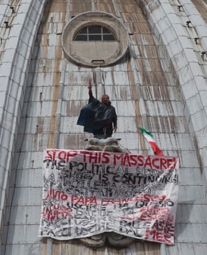 Italian businessman Marcello di Finizio stands by his banner with writings against the Italian Government and the Euro as he protests on St. Peter's 130-meter-high (42-feet-high) dome, at the Vatican, Tuesday, May 21, 2013.