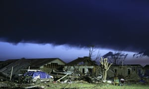 As dawn breaks, storm clouds roll in over a destroyed neighbourhood.