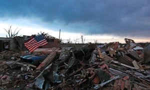 As the sun rises an American flag blows in the wind on top of the rubble of a destroyed home.