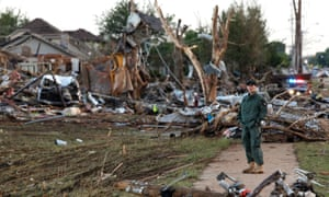 A member of a security team helps guard an area of rubble from a destroyed residential neighborhood.