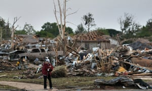 A local resident allowed by security officers into an otherwise sealed off neighborhood walks past the rubble of destroyed homes.