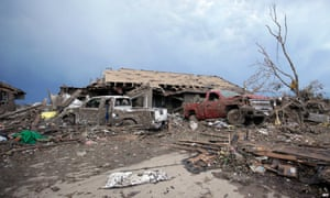 Cars and piles of debris lie around a home destroyed by the tornado.