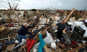 Dalton Sprading, right, hands a gun to his uncle Roger Craft as he salvages items from his tornado-ravaged home.