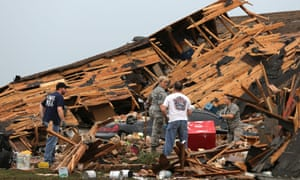 People sort through a home levelled the day after a killer tornado hit.