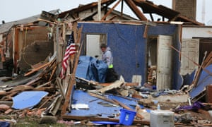 A man looks through debris for belongings in his home.